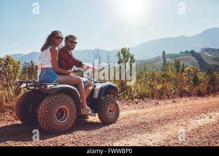 Portrait of loving couple in nature on a off road vehicle. Young man and woman enjoying a quad bike ride in countryside. - Stock Photo