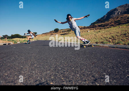 Young man and woman skateboarding on the rural road. Young couple enjoying skating on the road. - Stock Photo