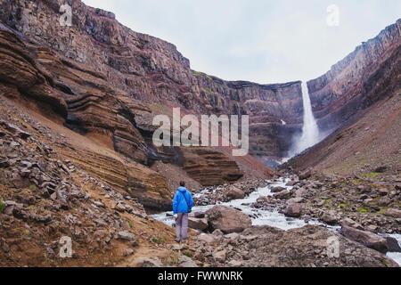 hiker walking to Hengifoss waterfall in Iceland, beautiful amazing landscape - Stock Photo