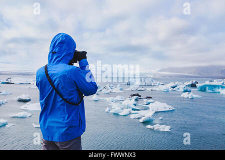 nature travel photographer, person taking photo of arctic icebergs in Iceland - Stock Photo