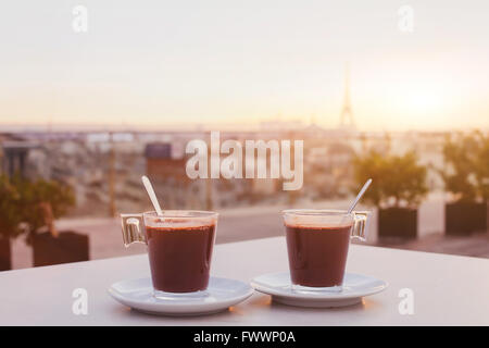 two cups of coffee or hot chocolate and Paris skyline at sunset, cafe with panoramic view of the city with Eiffel - Stock Photo