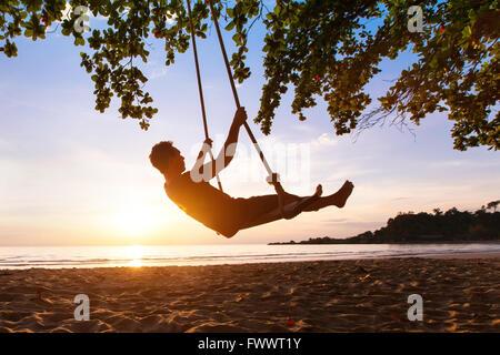 swing on paradise tropical beach at sunset, happy people enjoying summer - Stock Photo