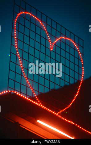 Light shaped to heart symbol on the roof of the house - Stock Photo