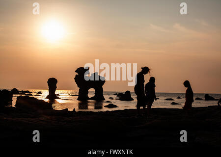 Sweden, Gotland, Faro, Gamle hamn, Silhouette of mother and children (8-9, 10-11) on beach at sunset - Stock Photo