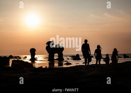 Sweden, Gotland, Faro, Gamle hamn, Silhouette of mother and children (2-3, 8-9, 10-11) on beach at sunset - Stock Photo
