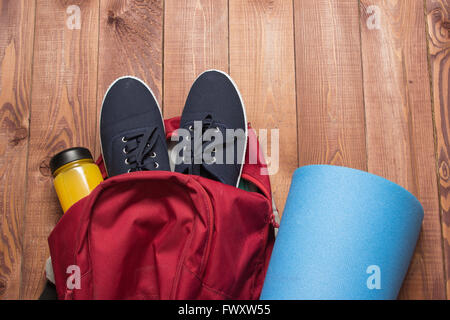 Sports bag with sports equipment: shoes, bottle, fitness mat on wooden floor - Stock Photo