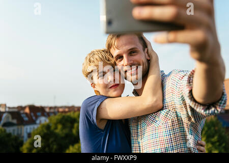 Germany, Berlin, Young couple hugging and taking selfie with smart phone - Stock Photo
