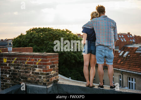 Germany, Berlin, Young couple standing on rooftop looking at view - Stock Photo