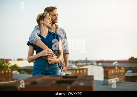 Germany, Berlin, Young couple standing on rooftop against sky - Stock Photo