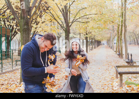 happy young couple playing and laughing together in autumn park - Stock Photo