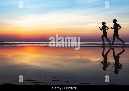 two runners on the beach, silhouette of people jogging at sunset, healthy lifestyle background with copyspace - Stock Photo