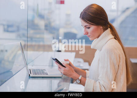 woman using smart phone in modern cafe inerior, mobile application, checking email - Stock Photo