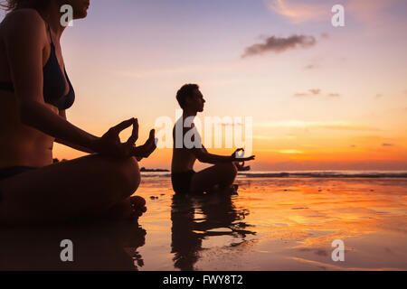 group of people meditating on the beach, yoga and health background - Stock Photo