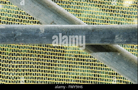 Detail of two steel scaffold pipes isolated on yellow sow background. - Stock Photo