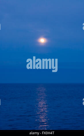 Soft moon in clouds and haze reflected in water on blue evening sky. - Stock Photo