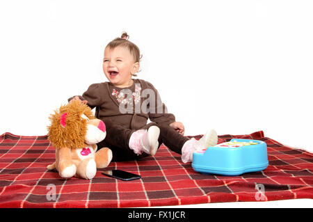 A little baby girl sitting on a blanket on the floor with her toy's and playing, isolated for white background. - Stock Photo