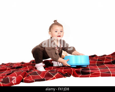 A lovely baby girl playing with her toy's on the blanket on the floor,isolated for white background. - Stock Photo