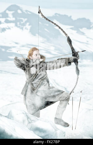Wild girl archer in the snow with bow - Stockfoto
