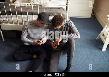 Two Male Students In Bedroom Check Messages On Mobile Phones - Stock Photo