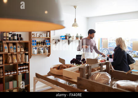 Male Sales Assistant Serving Female Customer In Delicatessen - Stock Photo