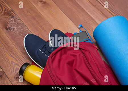 Sports bag with sports equipment: shoes, bottle, smart phone fitness mat on wooden floor - Stock Photo