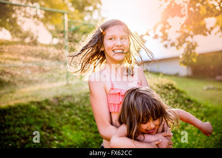 Two cute girls having fun outside in summer garden - Stock Photo