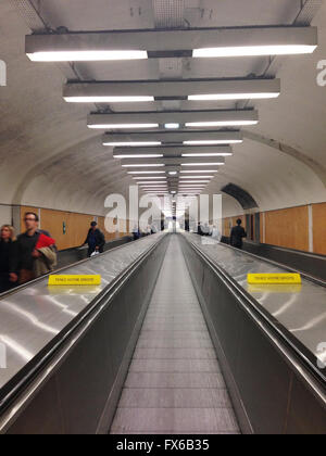 People are riding horizontal escalators in long passage in Chatelet subway station in Paris. - Stock Photo