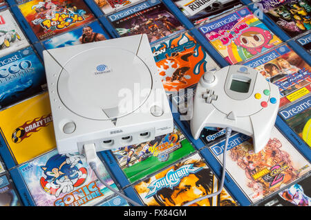 A European Sega Dreamcast console and hand controller are shown on a bed of PAL region games including Sonic Adventure. - Stock Photo