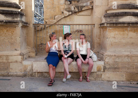 Three tourists take a break from touring in Valletta by sitting outside the ruins of the Royal Opera House. - Stock Photo
