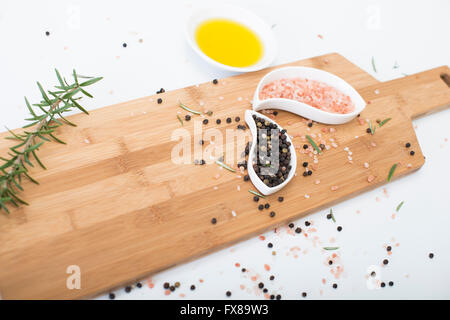 Himalayan rock salt and peppercorns, set against a white background. - Stock Photo