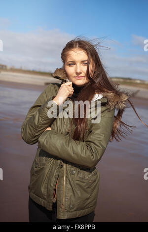 Beautiful young woman huddling in her coat on a windy day at the beach - Stockfoto