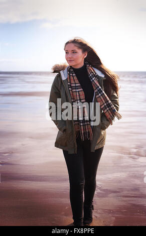 Young woman walking on a beach on a cold windy day - Stockfoto