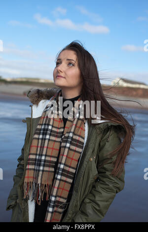 Beautiful young woman looking upwards whilst standing on the beach on a cold windy day - Stockfoto