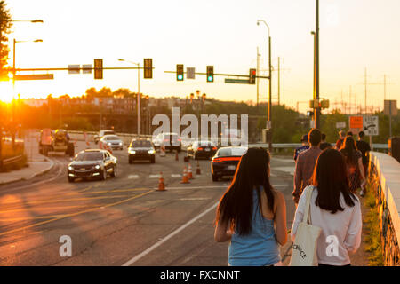 A group of people walk down a road in the sunlight, in Philadelphia. - Stock Photo
