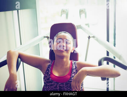 Tired woman resting at exercise equipment in gym - Stock Photo