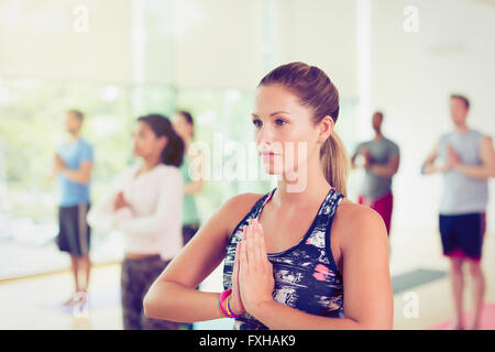 Focused woman with hands at prayer position in yoga class - Stock Photo