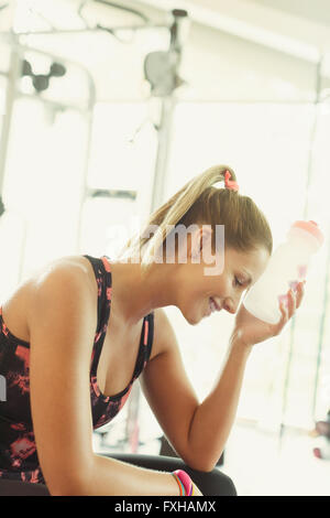 Tired woman cooling forehead with water bottle at gym - Stock Photo