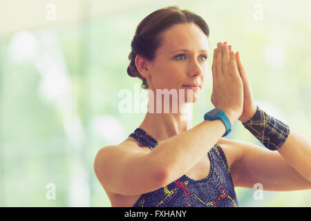 Calm woman with hands at prayer position in yoga class - Stock Photo