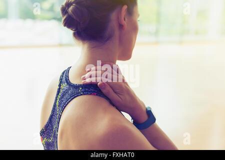 Woman rubbing neck at gym - Stock Photo