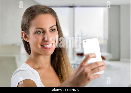 Single cute smiling woman taking a selfie in office with smart phone camera in hand up near her face - Stock Photo