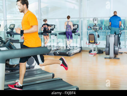 Man running on treadmill at gym - Stockfoto