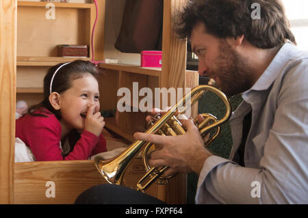 Father playing trumpet for little girl lying in bed - Stock Photo