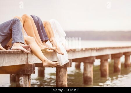 Group of friends relaxing on pier, focus on feet - Stock Photo