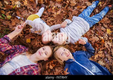 Four siblings lying on autumn leaves - Stock Photo
