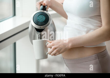 Close-up of torso of young pregnant model pouring water from electric stainless kettle after waking up. Future mom - Stock Photo