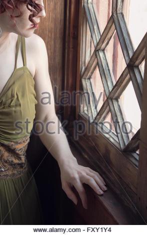 Woman in vintage 1940s dress by window - Stock Photo