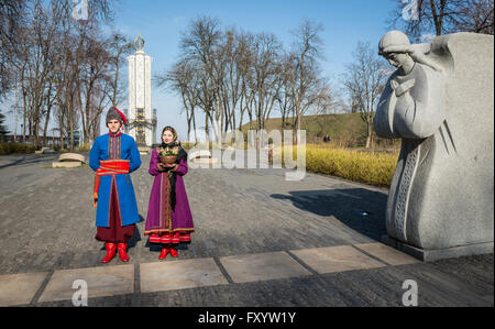Ukrainian man and woman wearing folk costumes in front of Monument to the Holodomor victims Kiev, Ukraine - Stock Photo