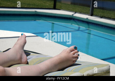 Feet of a mature woman wearing nail varnish on her toes to match the swimming pool colour. April 2016 - Stock Photo