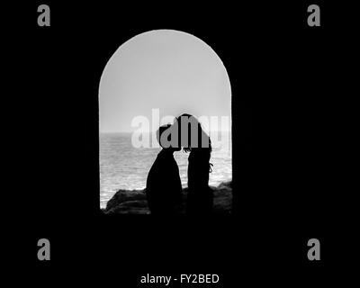 Silhouette of children couple giving a kiss with in a tunnel (black and white) - Stock Photo