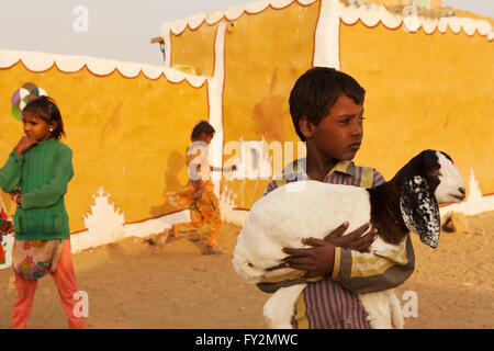 Unidentified children plays and the boy carry a baby lamb in his arms in a village near Thar desert, Jaisalmer, - Stock Photo